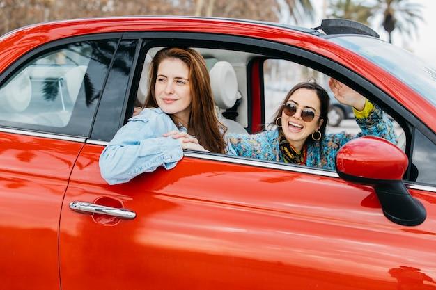 Deux femmes heureuses en regardant par la fenêtre de la voiture Photo gratuit