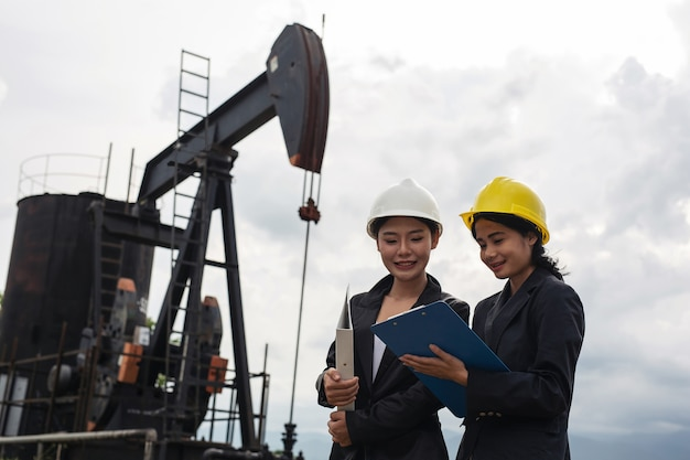 Deux femmes ingénieurs se tiennent à côté de pompes à huile en fonctionnement avec un ciel blanc. Photo gratuit