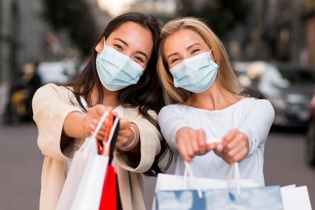 Deux Femmes Avec Des Masques Médicaux Posant Avec Des Sacs à Provisions Photo gratuit