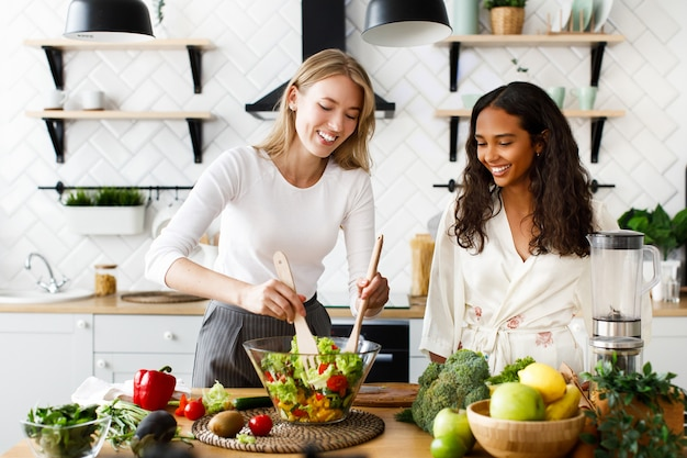 Deux Femmes De Nationalités Différentes Sourient Et Préparent Une Salade Dans La Cuisine Photo gratuit