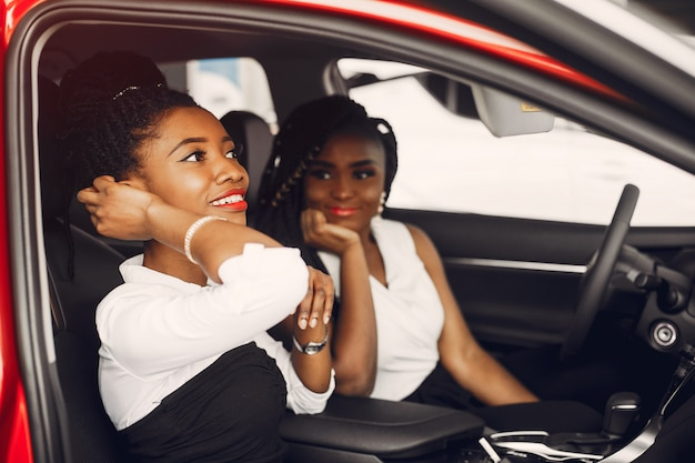Deux femmes noires élégantes dans un salon de l'automobile Photo gratuit