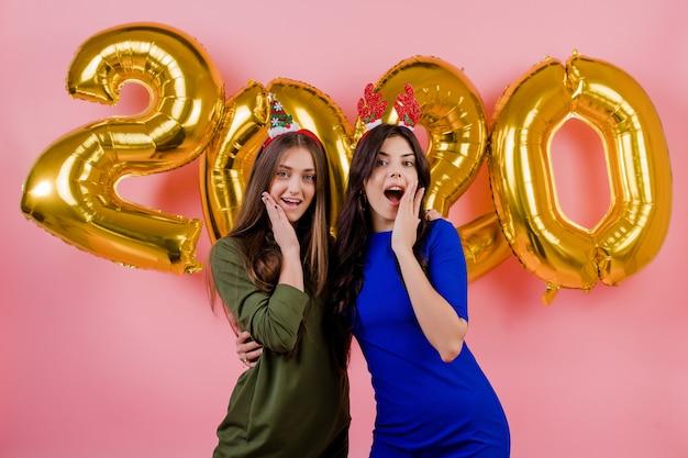 Deux, Femmes, Porter, Cerceau Noël, Et, étreindre, Devant, Doré, Ballons, 2020, Plus, Rose Photo Premium