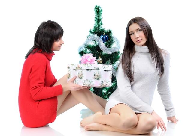 Deux Femmes Posant En Robes Assis Sur Le Sol Près D'un Arbre De Noël. Fille Donne Un Cadeau De Vacances Photo Premium