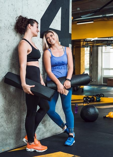 Deux femmes sportives avec tapis d'exercice s'appuyant sur le mur dans le club de fitness Photo gratuit