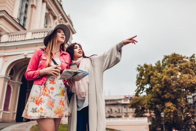 Deux femmes touristes cherchant le bon chemin en utilisant une carte à odessa. heureux amis voyageurs indiquant la direction Photo Premium