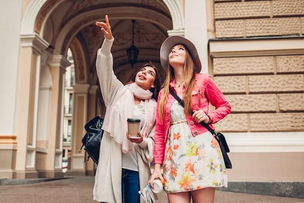 Deux femmes touristes discutant lors d'une visite touristique à odessa. heureux amis voyageurs pointant vers le haut Photo Premium