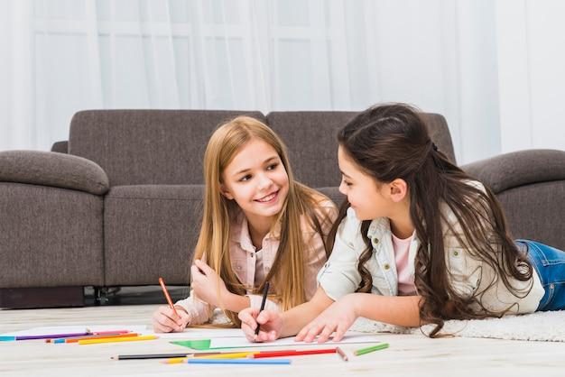 Deux filles allongées sur un tapis en train de dessiner avec des crayons de couleur dans le salon Photo gratuit