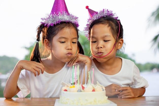 Deux filles asiatiques célèbrent leur anniversaire et soufflant des bougies sur le gâteau d'anniversaire de la fête Photo Premium