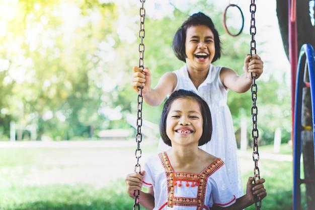 Deux filles asiatiques s'amusant sur une balançoire Photo Premium