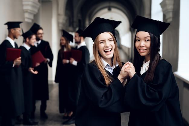 Deux filles dans le couloir de l'université en robe. Photo Premium