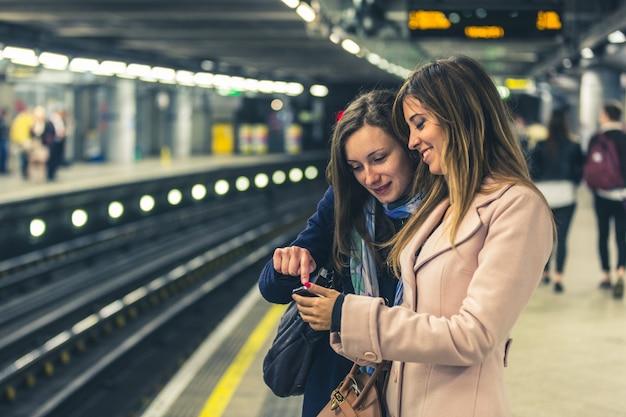 Deux filles dans le métro londonien attendant le train. Photo Premium