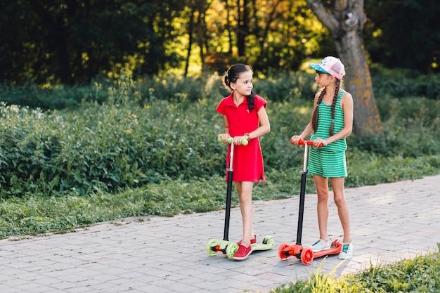 Deux, filles, debout, pousser, scooter, regarder, autre, dans parc Photo gratuit