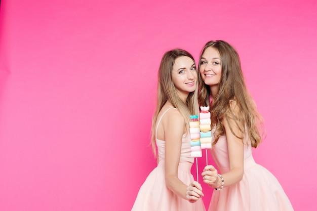 Deux filles douces aiment les poupées posant au rose avec de la guimauve. Photo Premium