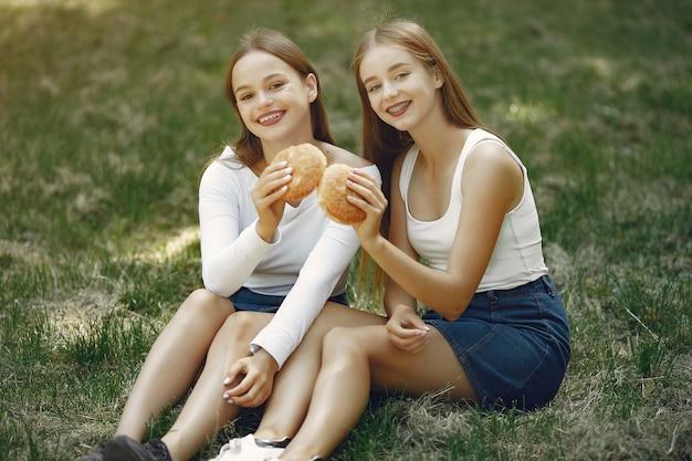 Deux filles élégantes dans un parc de printemps Photo gratuit