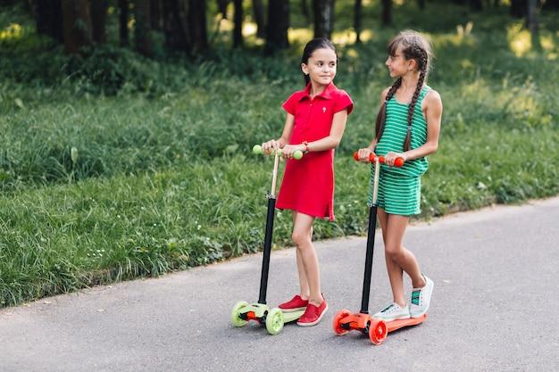 Deux, filles, équitation, coup, scooter, rue Photo gratuit