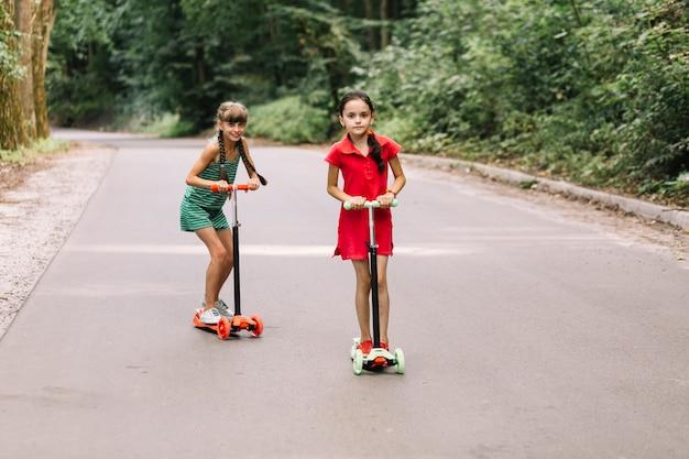 Deux, filles, équitation, scooters, rue droite Photo gratuit