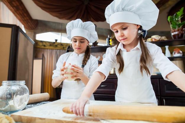 Deux filles font de la pâte à la farine. Photo Premium