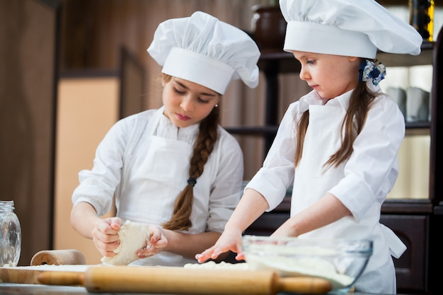 Deux Filles Font De La Pâte à Farine. Photo Premium