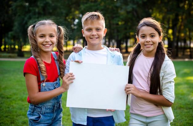 Deux filles et un garçon tenant une affiche dans leurs mains Photo gratuit