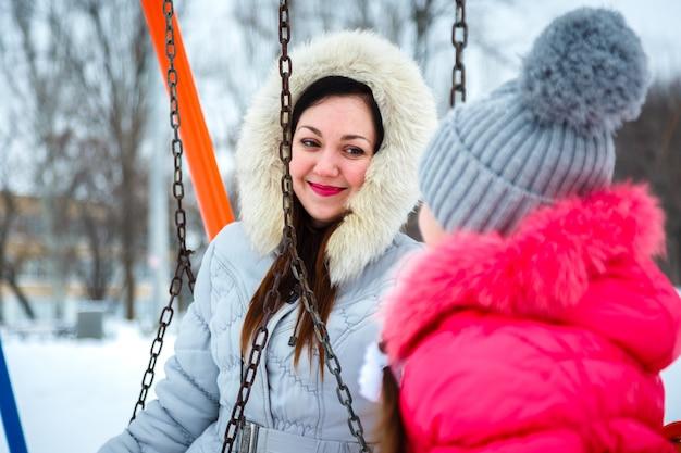 Deux filles heureuse, mère et fille, assis sur une balançoire sur une aire de jeux dans le parc de la ville. Photo Premium
