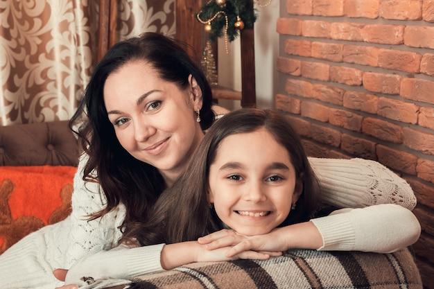 Deux Filles Heureuse, Mère Et Fille, S'installant Sur Un Canapé Dans La Salle Décorée De Noël. Photo Premium