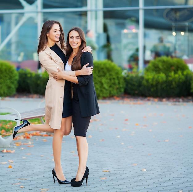 Deux Filles Heureuse Voyageant à L'étranger Ensemble, Transportant Une Valise à L'aéroport Photo Premium