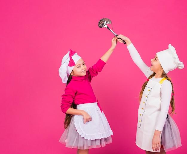 Deux Filles Heureux Cuisiniers Debout Avec Des Louches Photo gratuit