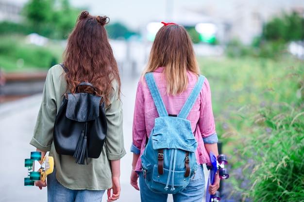 Deux filles hipster avec planche à roulettes à l'extérieur à la lumière du coucher du soleil. closeup skatebords dans les mains féminines. femmes sportives actives s'amusant ensemble dans le skate park. Photo Premium