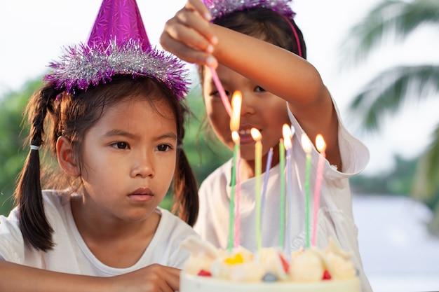 Deux filles mignonnes enfant asiatique allumer une bougie sur le gâteau d'anniversaire ensemble à la fête d'anniversaire Photo Premium