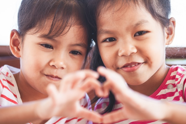 Deux filles mignonnes enfant asiatique en forme de coeur avec les mains avec amour Photo Premium