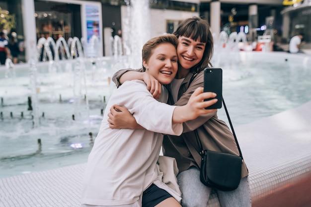 Deux Filles Prennent Un Selfie Dans Le Centre Commercial, Une Fontaine Photo gratuit