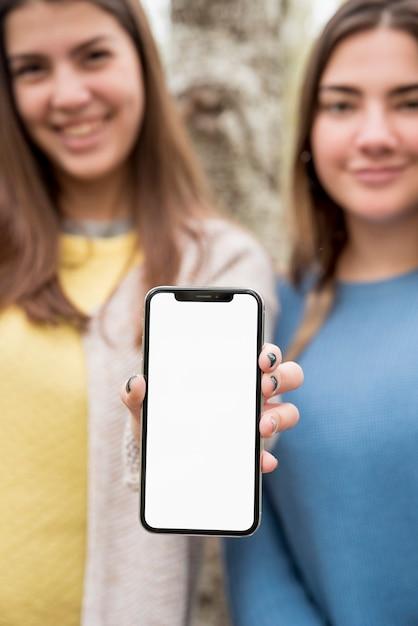 Deux filles présentant une maquette de smartphone Photo gratuit