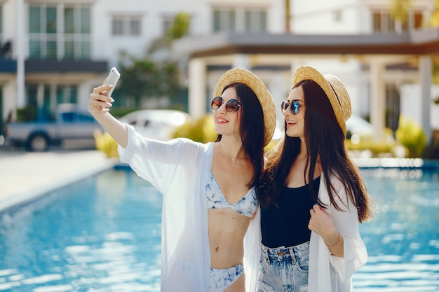 Deux filles se détendre au bord de la piscine et prendre des photos sur leur téléphone Photo gratuit