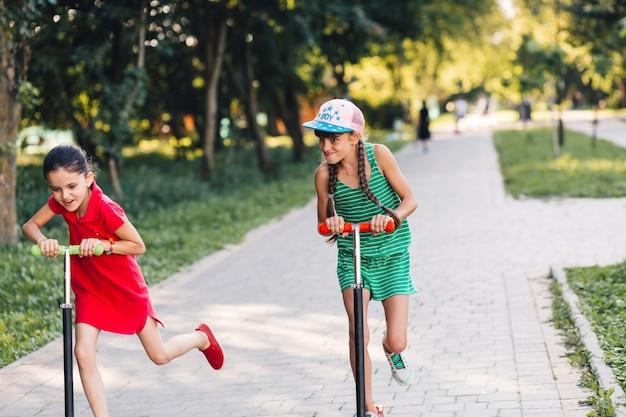 Deux filles se moquant en roulant sur une trottinette dans le parc Photo gratuit