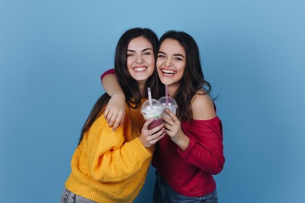 Deux filles se tiennent côte à côte et sourient pendant qu'elles boivent un milk-shake et un cocktail Photo gratuit