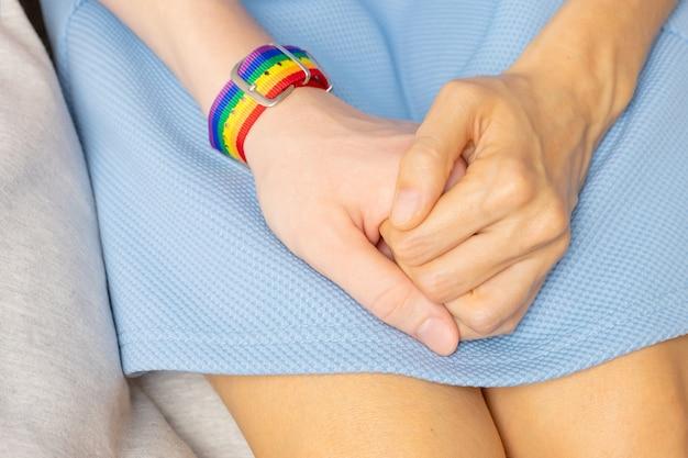 Deux Filles Se Tiennent La Main, D'une Part Il Y A Un Bracelet Lgbt. Le Concept D'amour, De Tolérance Sexuelle, D'homosexualité. Photo Premium
