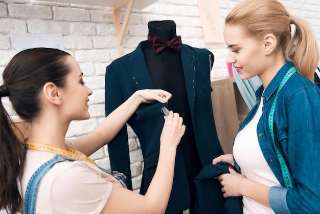 Deux filles à l'usine de vêtement desining nouvelle veste de costume homme. Photo Premium