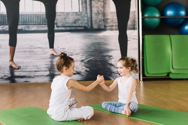 Deux fillettes assis sur un tapis de yoga et jouant dans une salle de sport Photo gratuit
