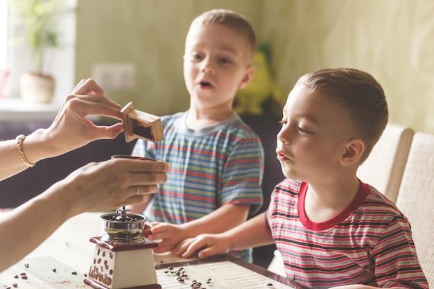 Deux frères aident sa mère à moudre du café Photo Premium