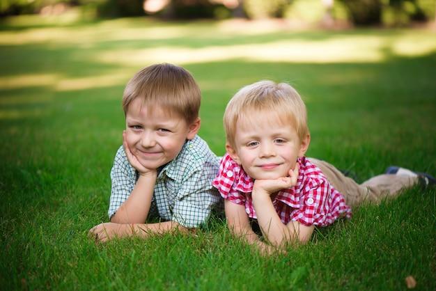 Deux frères allongés sur l'herbe dans un parc en plein air, souriant et Photo Premium