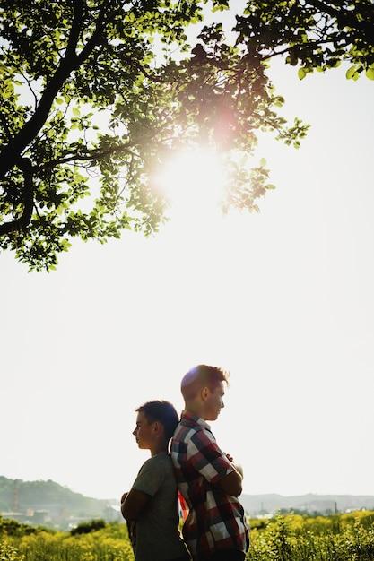 Deux frères ou amis se tiennent côte à côte sous un arbre vert dans les rayons du soleil du soir Photo gratuit