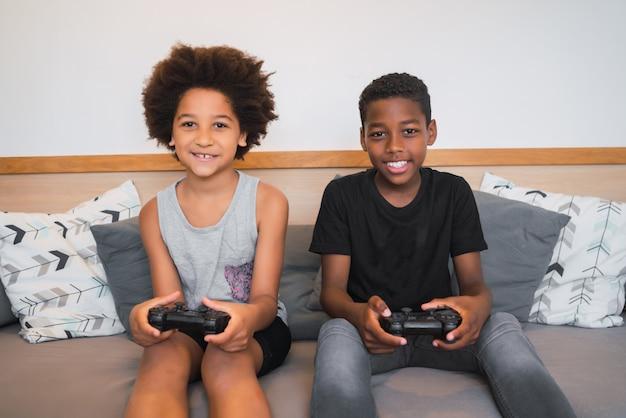 Deux Frères Jouant à Des Jeux Vidéo à La Maison. Photo Premium