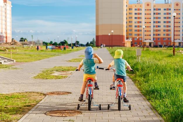 Deux frères jumeaux à vélo ensemble Photo Premium