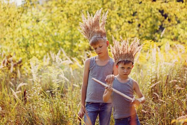 Deux frères ont une couronne d'herbe sèche sur la tête et des épées dans les mains. concept de joie et de jeu. Photo Premium