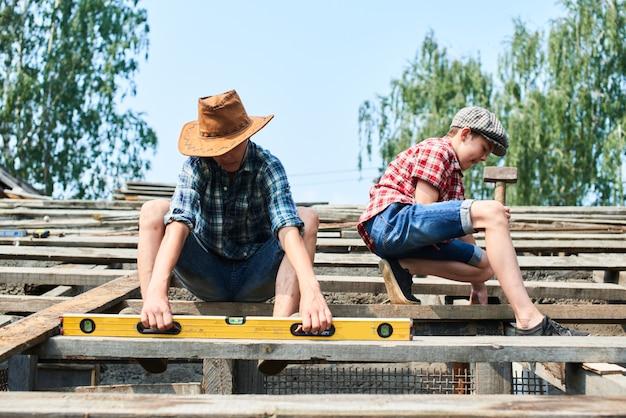 Deux Frères En Train De Construire Le Toit D'une Grange Dans Le Village Photo Premium
