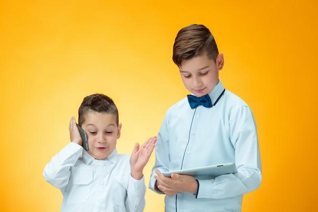 Les Deux Garçons à L'aide D'un Ordinateur Portable Sur Le Mur Orange Photo gratuit