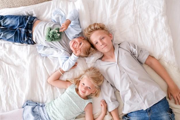 Deux garçons et une fille blonds sont couchés ensemble sur le lit, regardant et souriant. Photo Premium