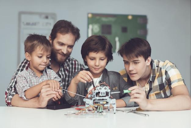 Deux garçons et un homme sont assis dans l'atelier et construisent un robot. Photo Premium