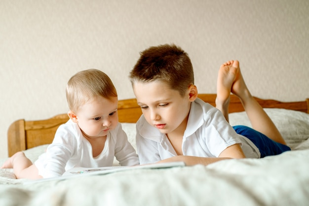 Deux garçons, lisant un livre, s'éduquant Photo Premium