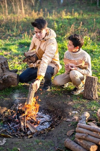 Deux Garçons Sur Un Pique-nique Allumant Un Feu De Camp Avec Des Troncs, De L'herbe Verte Photo Premium